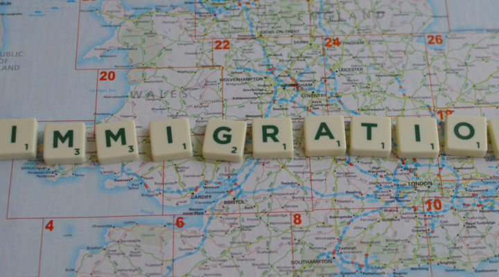 """immigration"" spelled in Scrabble letters over a map of Britain"